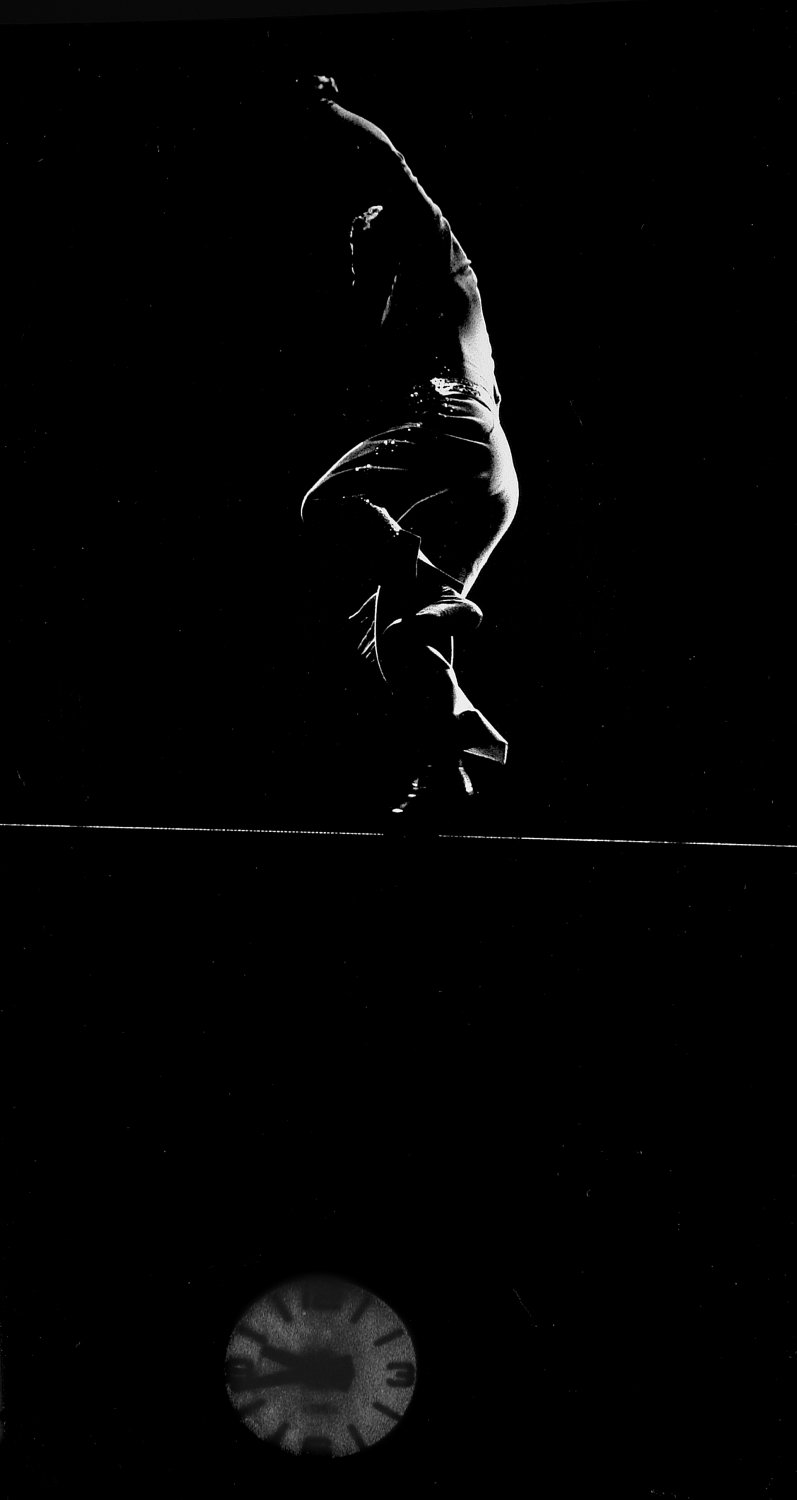 - Walking on the high wire. According to the clock below him, it's 9:45 pm. - Leo Stashin. Circus, Ringling Bros. Barnum and Bailey, Madison Square Garden, tightrope, trapeze. Alzana, black and white - - art  - photography - by Tony Karp