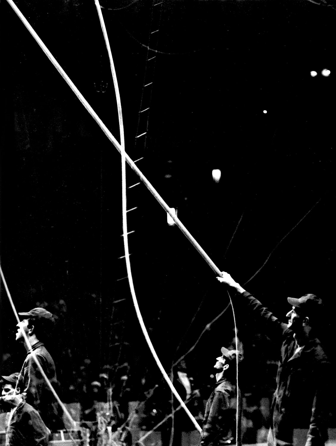 - The riggers working in the background, making sure that all the ropes and wires are in the proper places. - Leo Stashin. Circus, Ringling Bros. Barnum and Bailey, Madison Square Garden, tightrope, trapeze. Alzana, black and white - - art  - photography - by Tony Karp